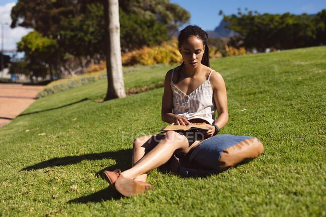 Donna afroamericana seduta sull'erba accigliata, che legge un libro nel parco. Tempo libero stile di vita ricreativo. — Foto stock