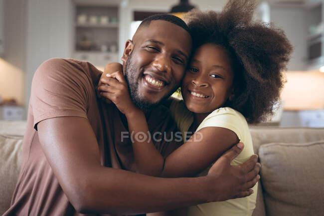 Африканский американец и его дочь обнимаются на диване. оставаться дома в изоляции во время карантинной изоляции. — стоковое фото