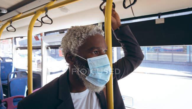 Ein älterer afroamerikanischer Mann mit Gesichtsmaske steht im Bus und schaut aus dem Fenster. digitaler Nomade unterwegs in der Stadt während Coronavirus covid 19 Pandemie. — Stockfoto