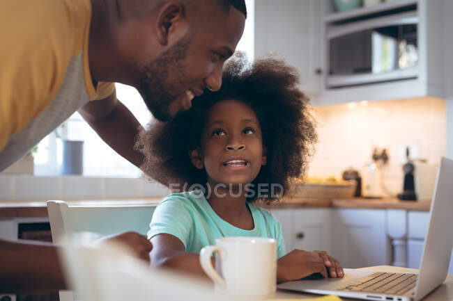 African american girl using laptop with her father. staying at home in self isolation during quarantine lockdown. — Stock Photo