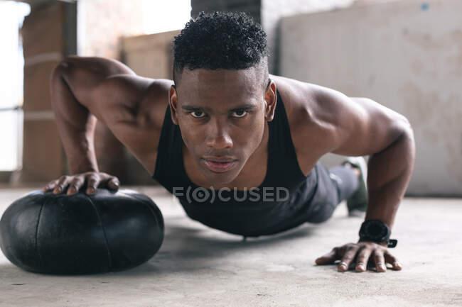 Портрет африканского американца, занимающегося отжиманиями с мячом. здоровый образ жизни. — стоковое фото