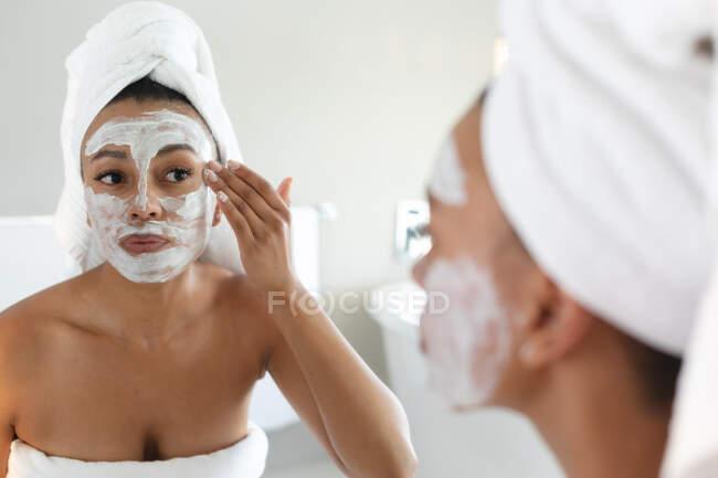 Mulher afro-americana aplicando máscara facial enquanto olha no espelho no banheiro. ficar em casa em auto-isolamento em quarentena — Fotografia de Stock