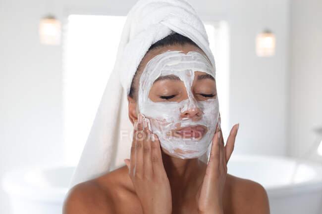Mulher afro-americana aplicando máscara facial no banheiro. ficar em casa em auto-isolamento em quarentena — Fotografia de Stock