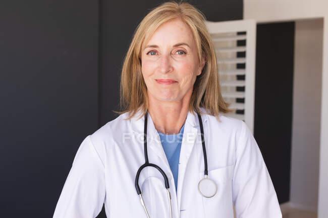 Médica branca, idosa, a olhar para a câmara e a sorrir. profissional médico a trabalhar durante a pandemia do coronavírus covid 19. — Fotografia de Stock