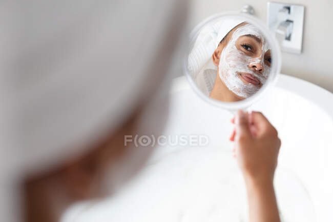 African american woman with face mask holding a mirror in bathroom. staying at home in self isolation in quarantine lockdown — Stock Photo