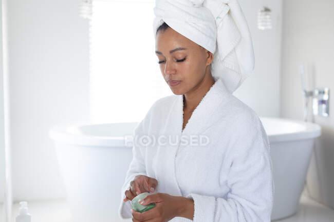 Donna afroamericana in accappatoio con crema viso in bagno. stare a casa in isolamento personale in quarantena — Foto stock