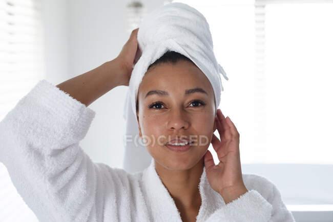Портрет африканской американки в халате, трогающей лицо в ванной. оставаться дома в изоляции в карантинной изоляции — стоковое фото