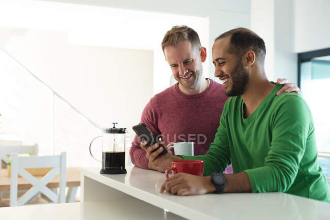 Multi ethnic gay male couple smiling and using smartphone in kitchen at home. staying at home in self isolation during quarantine lockdown. — Stock Photo