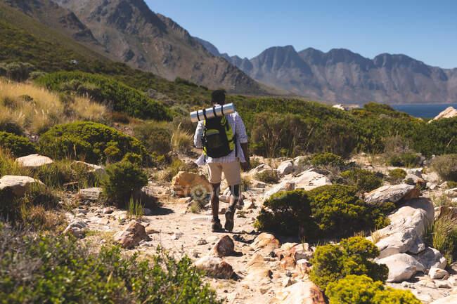 Uomo afroamericano che si allena all'aperto facendo escursioni su una montagna. allenamento fitness e stile di vita sano all'aperto. — Foto stock