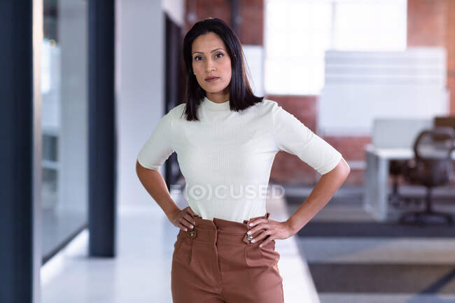Portrait of mixed race businesswoman with hands on hips. business person at work in modern office. — Stock Photo