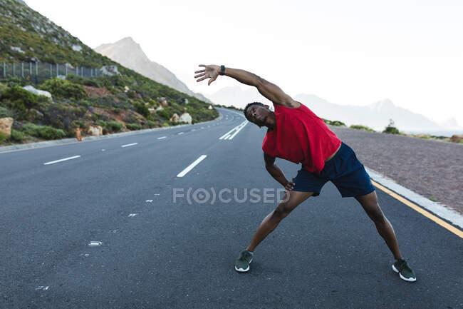 Un Afro-Américain qui fait de l'exercice en plein air sur une route côtière. entraînement physique et mode de vie sain en plein air. — Photo de stock