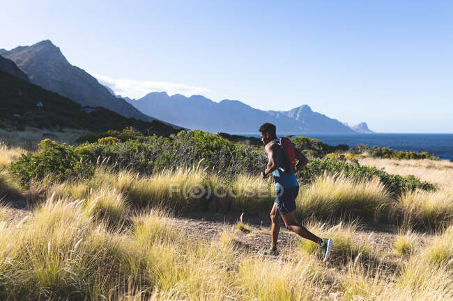 African american man exercising outdoors running on a mountain. fitness training and healthy outdoor lifestyle. — Stock Photo