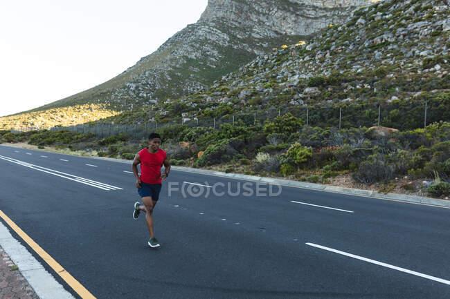 Uomo afroamericano che si allena all'aperto correndo su una strada costiera. allenamento fitness e stile di vita sano all'aperto. — Foto stock