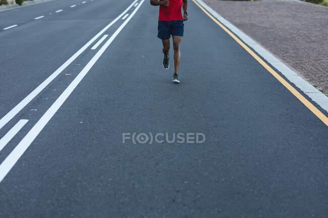 Un Afro-Américain faisant de l'exercice en plein air sur une route côtière. entraînement physique et mode de vie sain en plein air. — Photo de stock