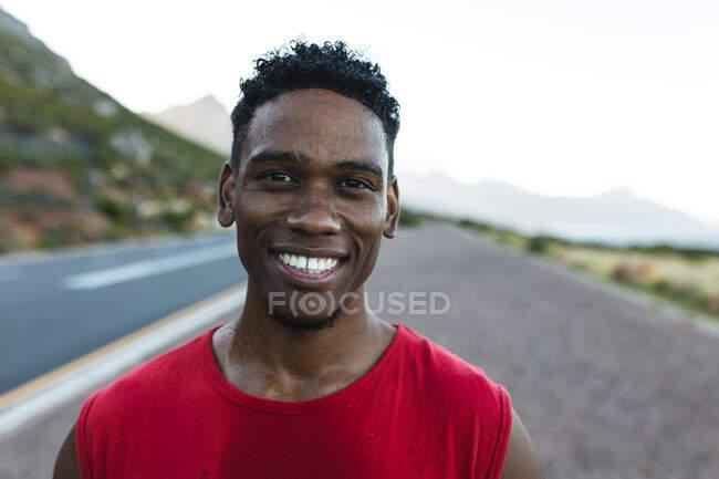 Porträt eines fitten afrikanisch-amerikanischen Mannes, der an einer Küstenstraße im Freien trainiert und in die Kamera lächelt. Fitnesstraining und gesunder Lebensstil im Freien. — Stockfoto