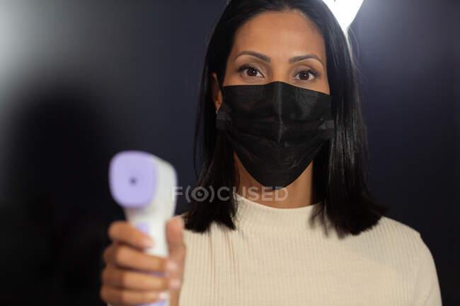 Porträt einer Geschäftsfrau mit Gesichtsmaske, die ein digitales Thermometer hält. Geschäftsmann bei der Arbeit im modernen Büro während der Covid 19 Coronavirus-Pandemie. — Stockfoto
