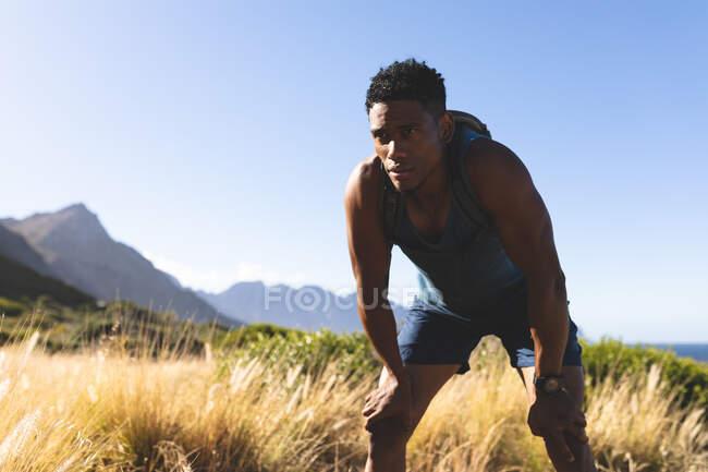 Hombre afroamericano haciendo ejercicio al aire libre descansando en una montaña. entrenamiento de fitness y estilo de vida saludable al aire libre. - foto de stock