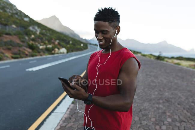 Африканский американец тренируется на открытом воздухе, используя смартфон на прибрежной дороге. фитнес-тренировки и здоровый образ жизни. — стоковое фото