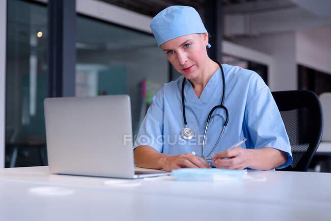 Médica branca na mesa usando laptop tomando notas durante a consulta de videochamada. telemedicina durante o bloqueio de quarentena. — Fotografia de Stock