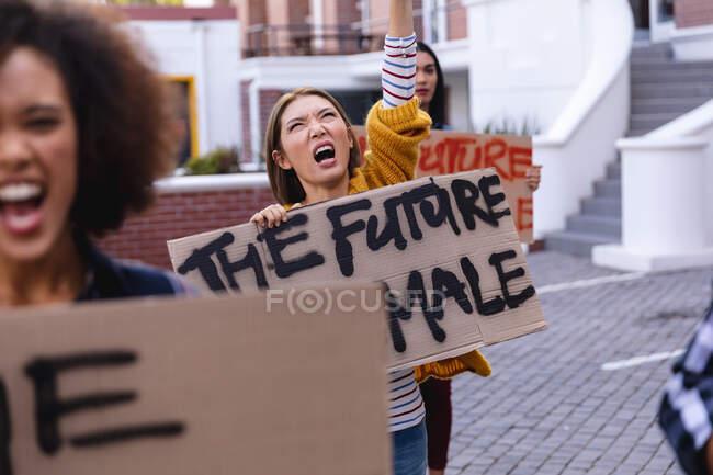 Кавказька жінка-протестувальник під час маршу, тримаючи саморобний знак протесту і вигукуючи з піднятою рукою. рівність прав і демонстраційний марш справедливості. — стокове фото