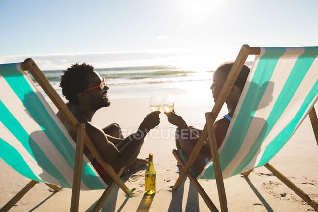 Афроамериканська пара закохана в те, що вона сидить у кафедрах і насолоджується напоями на пляжі. Любов, романтика і перерва на пляжі Літні канікули. — стокове фото