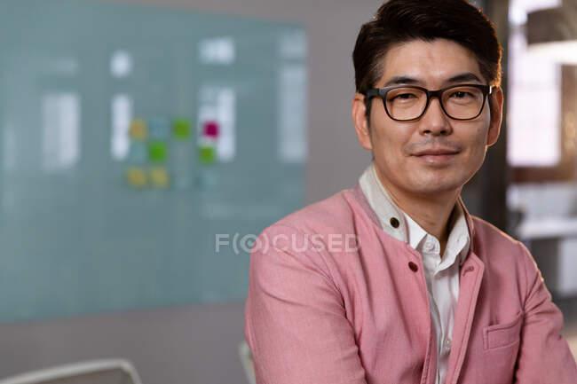 Retrato de elegante hombre de negocios asiático sonriendo a la cámara. persona de negocios en el trabajo en la oficina moderna. - foto de stock