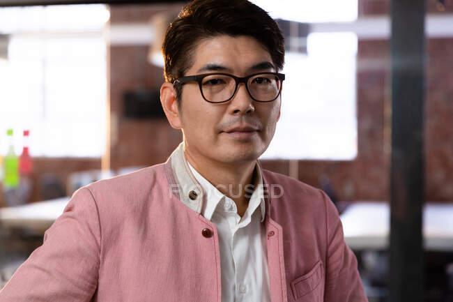 Ritratto di elegante uomo d'affari asiatico in cerca di fotocamera. uomo d'affari al lavoro in ufficio moderno. — Foto stock