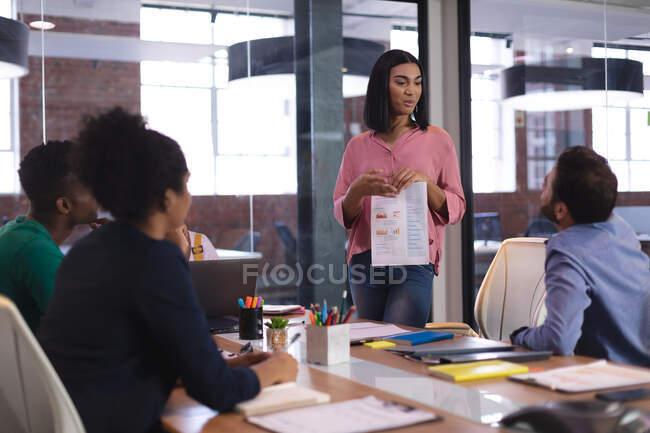 Gemischte Rasse Frau bei der Präsentation vor einer Gruppe von Kollegen im Besprechungsraum. unabhängiges kreatives Designgeschäft. — Stockfoto