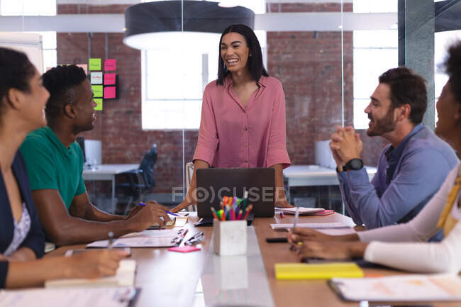Happy mixed race businesswoman speaking to diverse group of colleagues in meeting room using laptop. independent creative design business. — Stock Photo