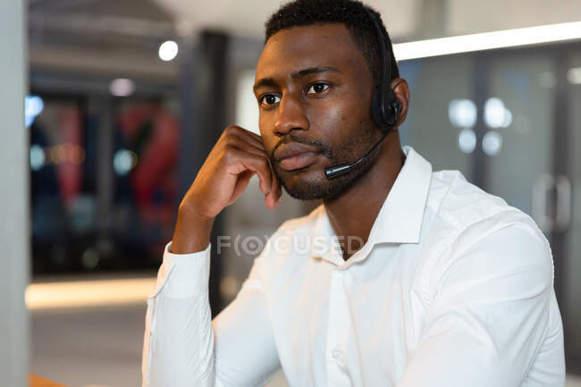 Casual african american businessman wearing phone headset sitting at desk. business person at work in modern office. — Stock Photo