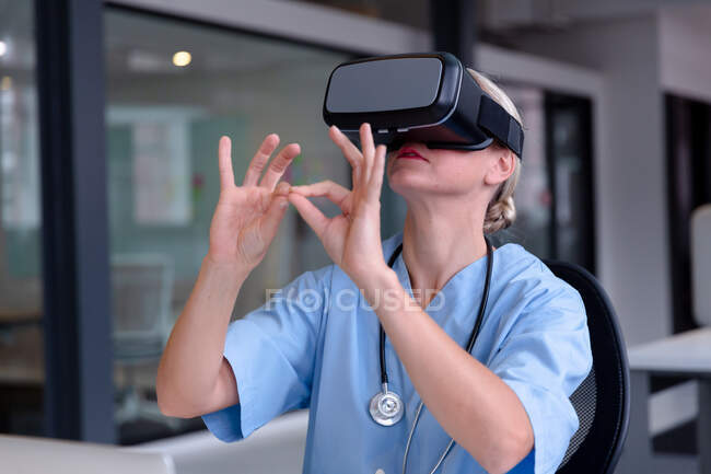 Medico donna caucasica che indossa scrub utilizzando auricolare vr e interfaccia virtuale. medico professionista al lavoro con la tecnologia. — Foto stock