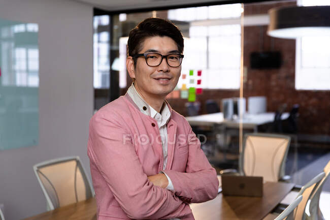 Портрет стильного азіатського бізнесмена, який посміхається фотоапарату. Бізнесмен на роботі в сучасному офісі.. — стокове фото