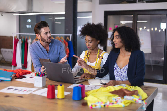Diverse group of fashion designer colleagues in discussion at work using digital tablet and laptop. independent creative design business. — Stock Photo