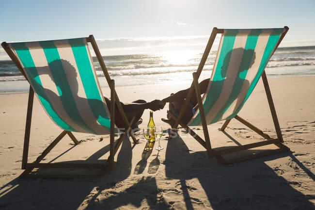 Coppia afroamericana innamorata seduta sulle sedie a sdraio, che si tiene per mano sulla spiaggia. amore, romanticismo e vacanze al mare vacanze estive. — Foto stock