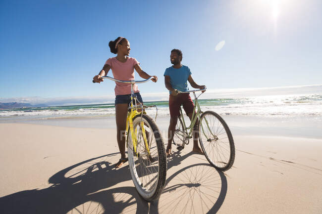 Happy african american couple on beach riding bicycle. healthy outdoor leisure time by the sea. — Stock Photo