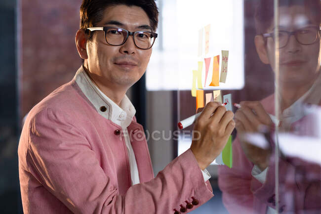 Retrato de elegante hombre de negocios asiático sonriendo y escribiendo notas en la pared de cristal. persona de negocios en el trabajo en la oficina moderna. - foto de stock