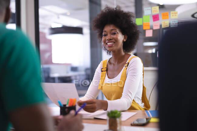 Porträt einer glücklichen afrikanisch-amerikanischen Geschäftsfrau im Besprechungsraum, die ein Dokument in die Kamera hält. unabhängiges kreatives Designgeschäft. — Stockfoto