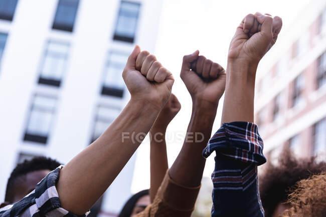 Підняті кулаки різних чоловіків і жінок-протестувальників демонструють на марші. рівність прав і демонстраційний марш справедливості. — стокове фото
