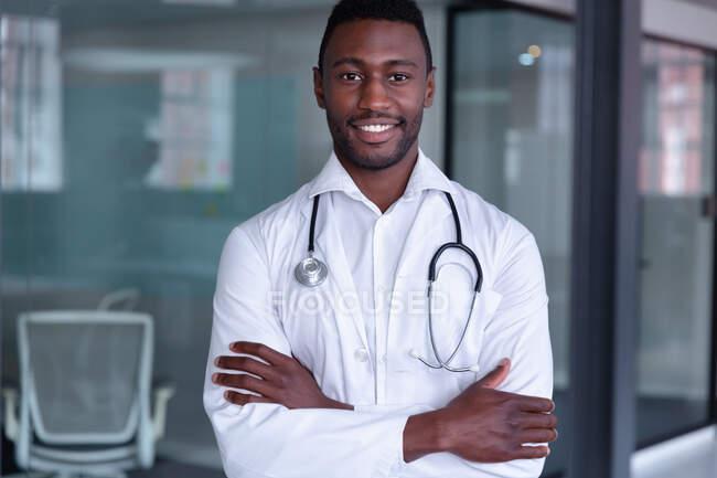 Ritratto di felice medico afroamericano di sesso maschile con stetoscopio sorridente a braccia incrociate. medico professionista sul lavoro. — Foto stock