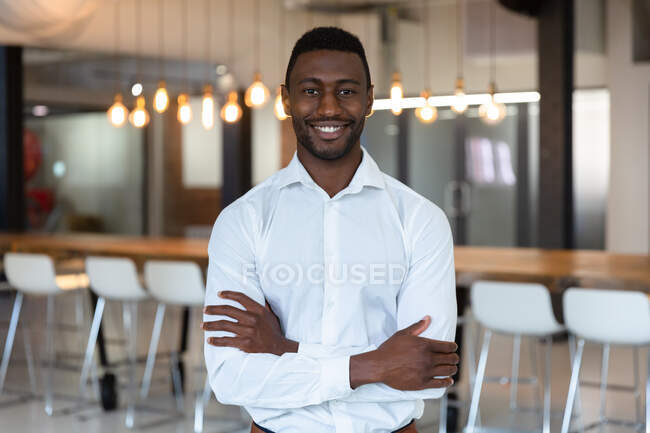Portrait of happy casual african american businessman with arms crossed smiling to camera. business person at work in modern office. — Stock Photo