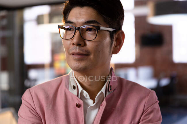 Portrait of confident stylish asian businessman looking to side. business person at work in modern office. — Stock Photo