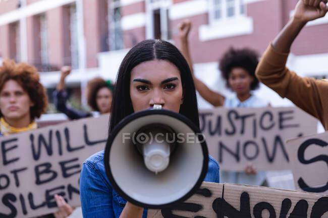 Змішана расова жінка використовує мегафон з протестувальниками під час маршу, тримаючи знак протесту і піднімаючи кулаки. рівність прав і демонстраційний марш справедливості. — стокове фото