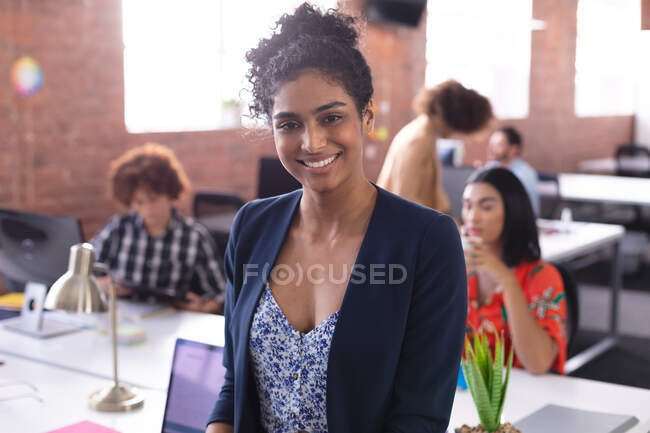 Portrait of mixed race businesswoman at the office looking to camera smiling. independent creative design business. — Stock Photo
