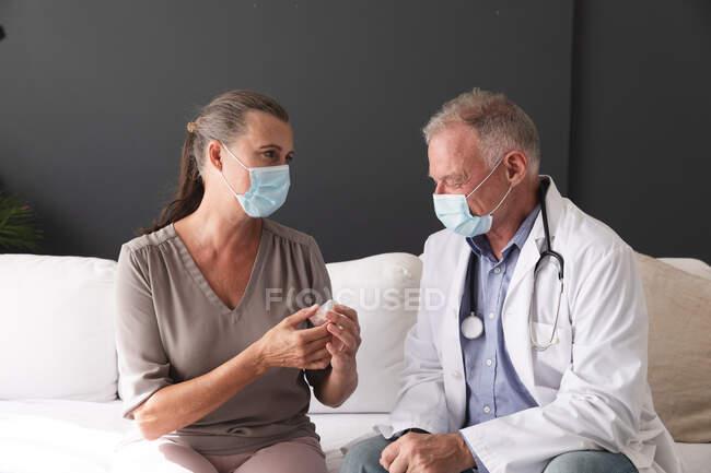 Médico do sexo masculino e paciente do sexo feminino caucasiano segurando medicação conversando, ambos usando máscaras faciais. profissional médico a trabalhar durante a pandemia do coronavírus covid 19. — Fotografia de Stock