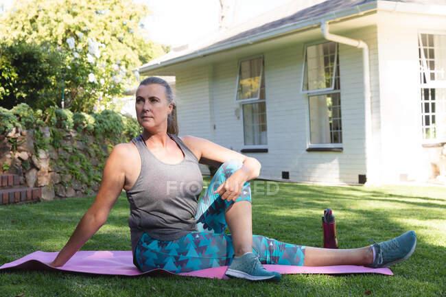 Старшая белая женщина, занимающаяся спортом в саду, сидящая на коврике для йоги. оставаться дома в изоляции во время карантинной изоляции. — стоковое фото