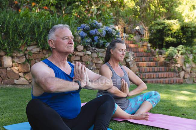 Счастливая старшая кавказская пара в саду практикующая йогу, сидящая и медитирующая. оставаться дома в изоляции во время карантинной изоляции. — стоковое фото