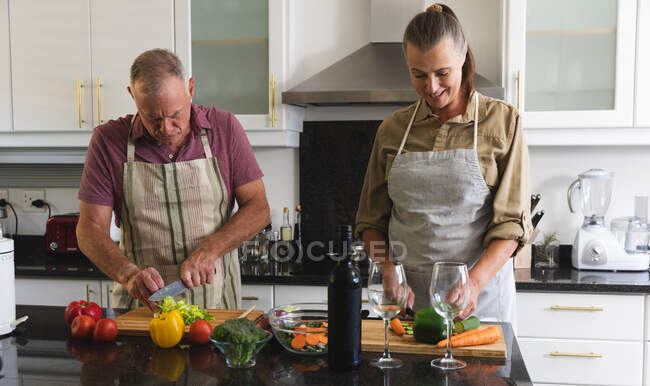 Happy caucasian senior couple in kitchen wearing aprons preparing food together. staying at home in isolation during quarantine lockdown. — Stock Photo