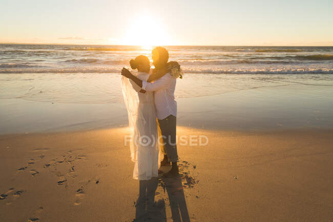 African american couple in love getting married, hugging on beach during sunset. love, romance and wedding beach break summer holiday. — Stock Photo