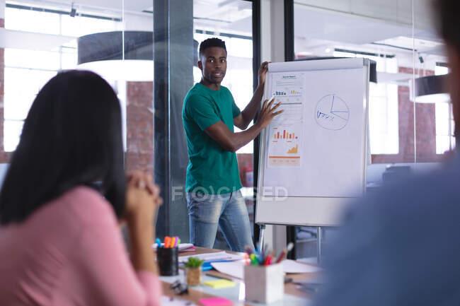 Африканський американський бізнесмен на білому дошці дає презентацію різним колегам. Незалежний бізнес творчого дизайну. — стокове фото