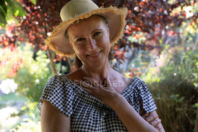 Portrait of happy caucasian senior woman standing in sunny garden wearing sunhat, smiling to camera. staying at home in isolation during quarantine lockdown. — Stock Photo